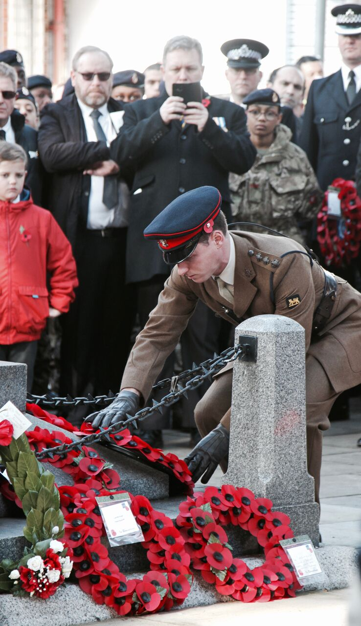 A soldier places a wreath at the foot of the West Lane War Memorial